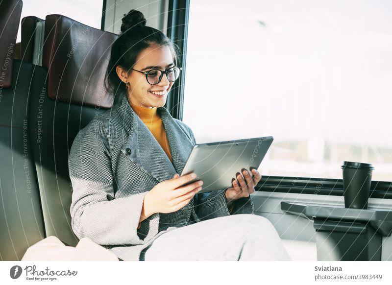 Junges Mädchen im Zug kommuniziert auf dem Tablet mit Freunden und Verwandten während der Fahrt im Zug Tablette Frau Passagier Glück reisend lesen eBook