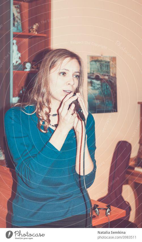 Junges Mädchen singt zu Hause in ein Mikrofon. Retro getöntes Bild. 20s 25-29 Jahre Taille hoch Erwachsener attraktiv schön Schönheit niedlich gefühlvoll Frau