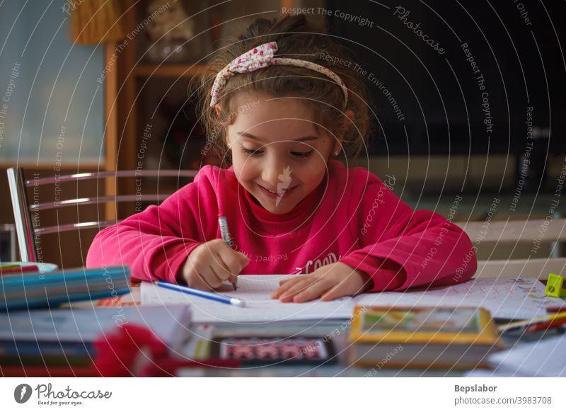Lächelnde 6 Jahre altes Mädchen macht ihre Hausaufgaben Kind schreiben schreibend Tisch Fall Farben Füllfederhalter Lernen lernen Schulmädchen Schreibtisch