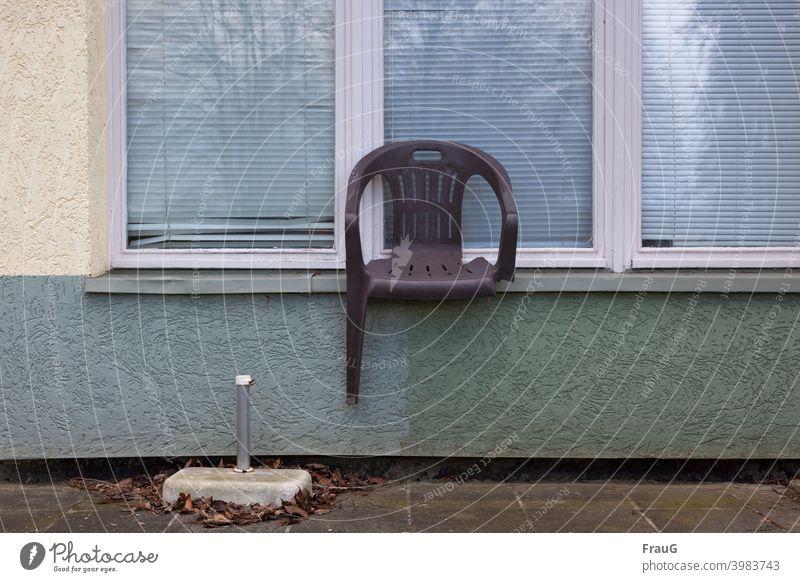 ein kaputter Stuhl auf der Fensterbank Haus Putzfassade Fassade Jalousien Spiegelung Gartenstuhl Stapelstuhl Kunststoff einbeinig alt Sonnenschirm-Ständer Laub