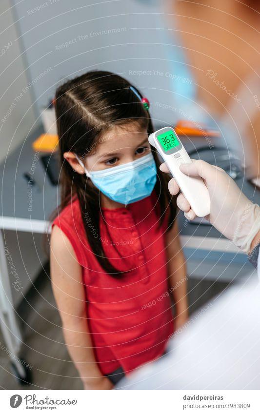 Mädchen ohne Fieber, dessen Temperatur vom Arzt gemessen wird berührungsloses Thermometer kein Fieber Schutzmaske Messung Coronavirus ärztliche Untersuchung