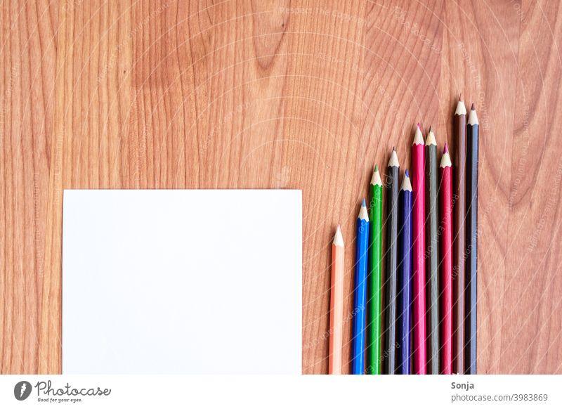 Buntstifte und ein leeres Papierblatt auf einem Holztisch Kreativität Schreibwaren Farbfoto Zettel zeichnen Freizeit & Hobby malen Kunst Schule bunt Kindheit