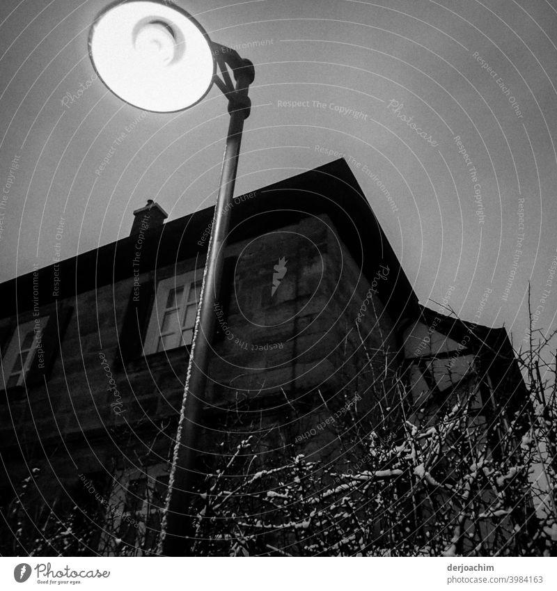 Die Nacht kommt. Eine Laterne ist schon an und beleuchtet das halbdunkle Haus. Neben der Laterne steht ein Baum auf dem noch etwas Schnee liegt. Laternenlicht