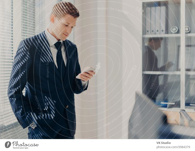 Konzentrierter männlicher Chef, hält Hand in Tasche, fokussiert in Bildschirm von Smartphone, sucht nützliche Informationen für neues Startup, posiert in Büro, elegant gekleidet. Mann plaudert am Handy am Schrank