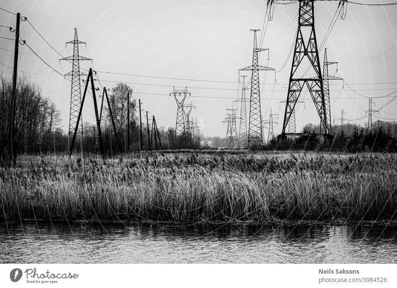 Hochspannungsleitungen, die den Fluss überragen Hintergrund blau Gebäude Kabel Küstenlinie Konstruktion Gefahr Tag Verteilung elektrisch Elektrizität Energie