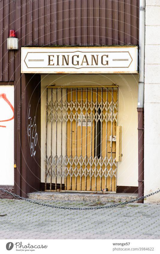 Die mit einem Scheerengitter gesicherte und verschlossene Eingangstür einer Spielothek Tür alt Holz Farbfoto geschlossen Außenaufnahme Menschenleer Tag