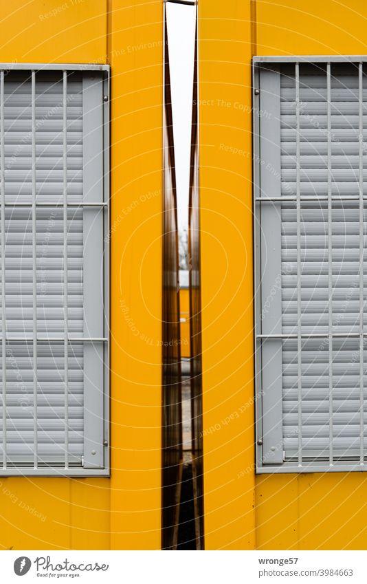 Blick durch den freien Spalt zwischen 2 gelben Baucontainern mit verschlossenen und vergitterten Fenstern Container Gelbe Container Freiraum Abstand Durchblick