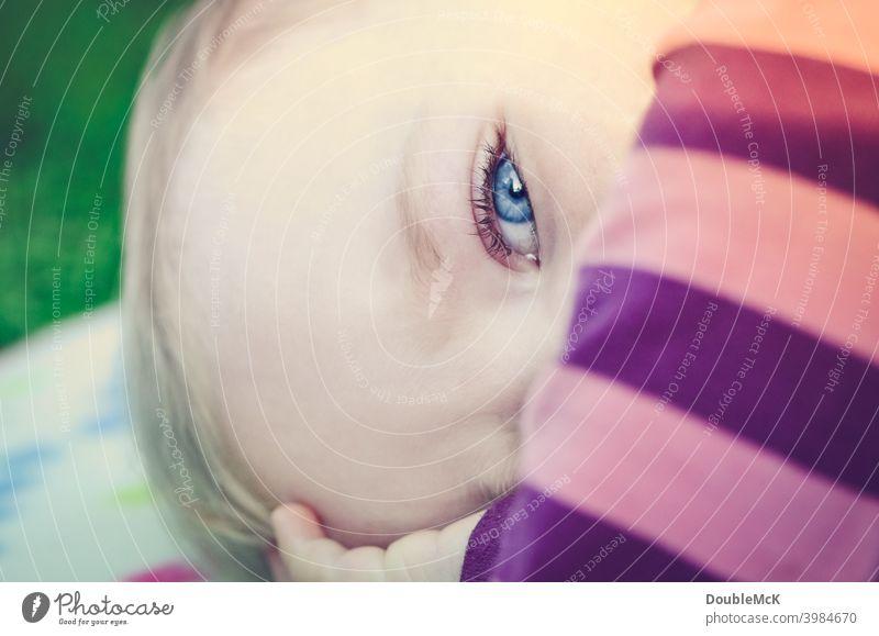 Ein Kleinkind liegend auf einer Picknickdecke in der Nahaufnahme Mädchen Gesicht Kindheit Mensch 1 1-3 Jahre Farbfoto Außenaufnahme Tag Schwache Tiefenschärfe