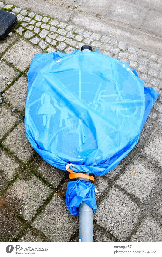 Ein mit einem blauen transparenten Müllsack verhülltes Verkehrszeichen (Verkehrsschild Nr. 241-31) liegt auf grauem Kopfsteinpflaster Fuß- und Radweg