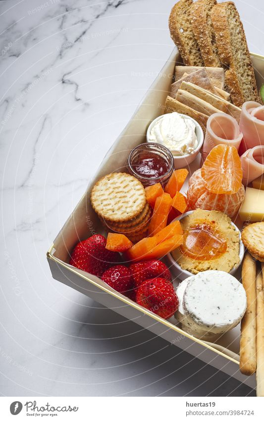 Gesunde Brunch-Box zum Mitnehmen Lebensmittel Mittagessen wegnehmen Lunch-Box Kiwi erdbeeren Schinken Brot Cookies Käse Karotten Mandarinen Humus Versand