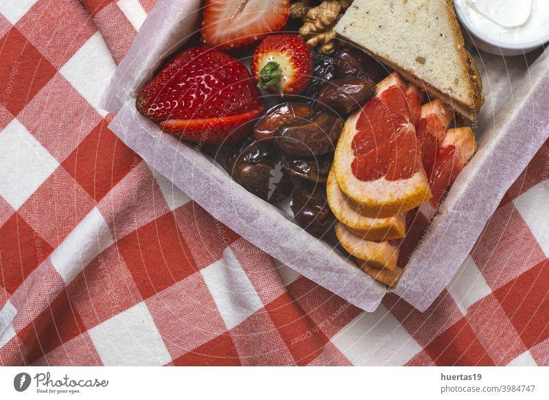 Gesundes Frühstück Brunch zum Mitnehmen verpackt Lebensmittel wegnehmen Lunch-Box Croissants Brötchen Frischkäse erdbeeren Datteln Frucht Walnüsse Daten Brot