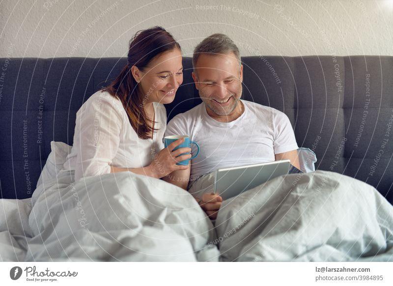 Glückliches Paar mittleren Alters, das morgens im Bett sitzt, Kaffee trinkt und mit einem digitalen Tablet Online-Einkäufe tätigt Sofa Möbel Familie Raum