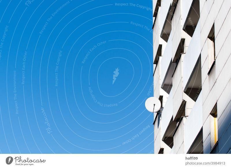 einsame Satellitenantenne an einer Hochhausfassade Urbanisierung Vereinsamung Tristesse Fassade blau Blauer Himmel modern Moderne Architektur Linie Stadt