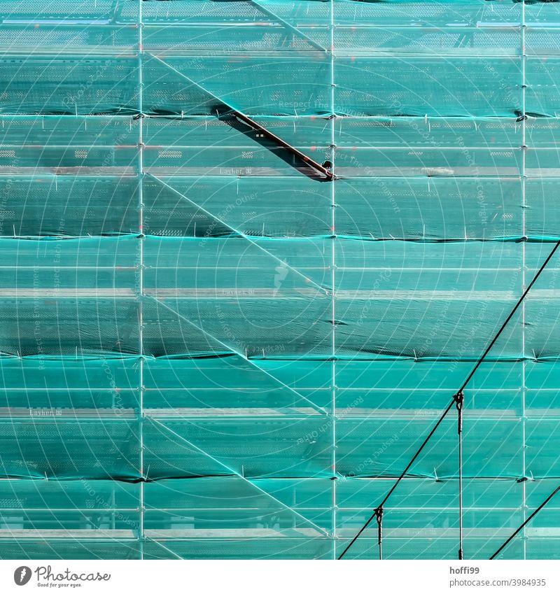 grünes Sicherheitsnetz vor einer eingerüsteten Fassade Netz Baustelle Gerüst Gerüstplane Baugerüst Strukturen & Formen Renovieren Abdeckung Gebäude Sanieren