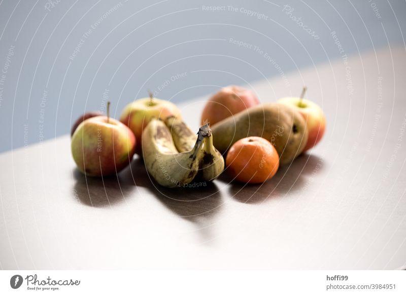 Früchte auf dem Tisch im Büro Frucht Banane Apfel Mandarin Birne Ernährung Lebensmittel Vegetarische Ernährung Bioprodukte Gesundheit lecker frisch Menschenleer