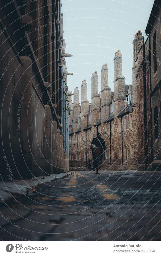 Dunkle stimmungsvolle Winteratmosphäre in der Trinity Lane, schmale berühmte Straße im Zentrum der Stadt Cambridge. Verbinden Universitäten, berühmte Touristenziel Ort. Person zu Fuß in der Ferne