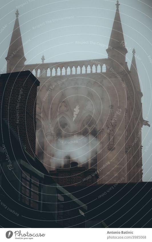 Vertikale Aufnahme von Rauch, der aus einem Schornstein kommt, Haus im Zentrum der Stadt Cambridge, berühmter Kirchturm im Hintergrund. Vorstadt Stadtzentrum
