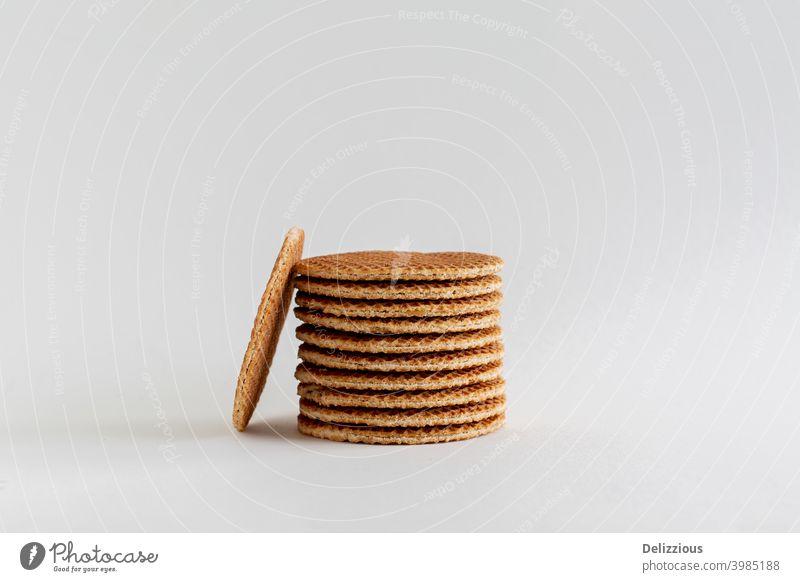 Ein Stapel holländischer Stroopwafels (Sirup- oder Karamellwaffeln) mit einem Keks an der Seite auf weißem Hintergrund mit Kopierraum, Nahaufnahme backen