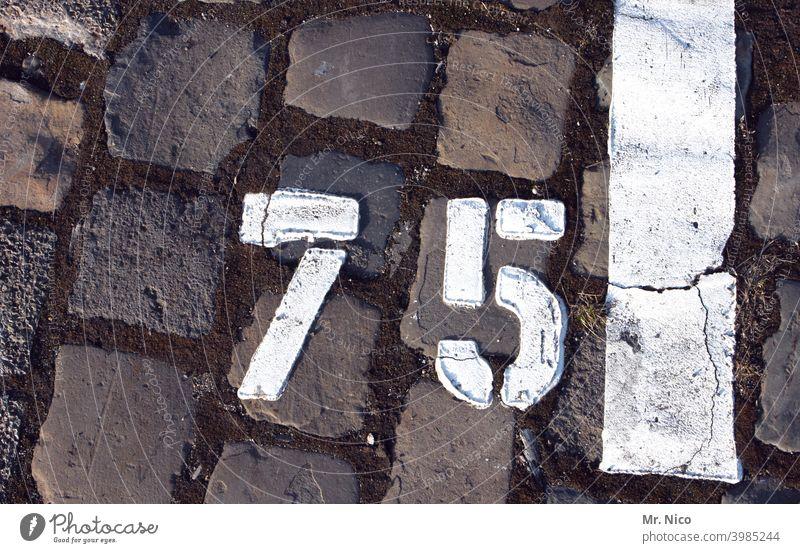 Nummer 75 Ziffern & Zahlen schwarz Parkplatz parken weiß grau Pflastersteine Jubiläum Stein Strukturen & Formen Platz Bodenbelag Ordnung Wege & Pfade