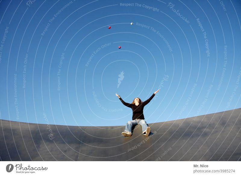 Sitzjonglage jonglieren Blauer Himmel Spielen Freizeit & Hobby werfen Ball arme ausbreiten sitzen Blick nach oben blau Bewegung Konzentration hochwerfen
