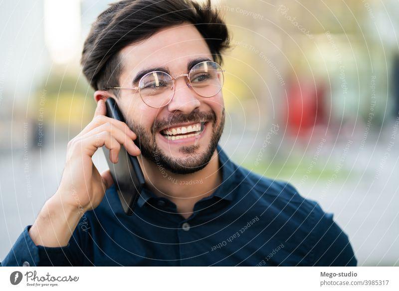 Junger Mann beim Telefonieren im Freien. jung Mobile urban Lächeln Anschluss Apparatur Porträt positiv Drahtlos Beteiligung laufen Blick Tippen sprechend reden
