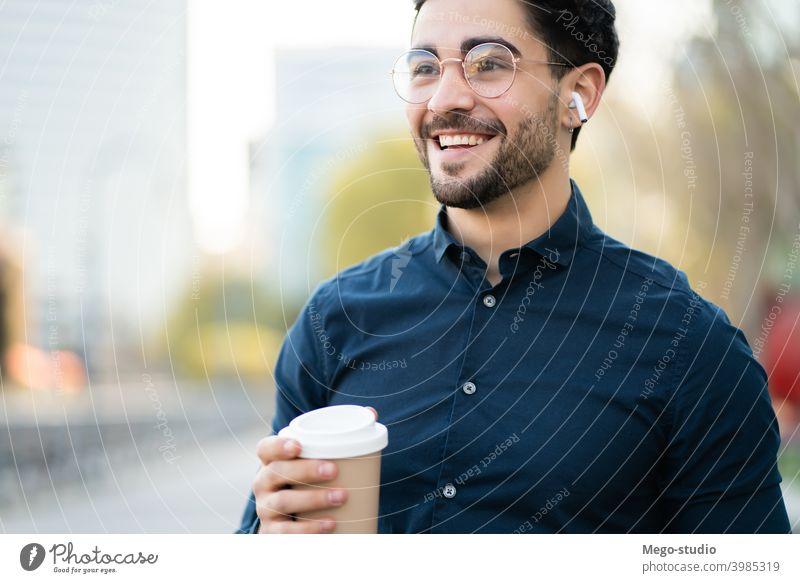 Junger Mann hält eine Tasse Kaffee, während er im Freien spazieren geht. Porträt jung urban wegnehmen abschließen Getränk Nahaufnahme Ohrhörer Freizeit