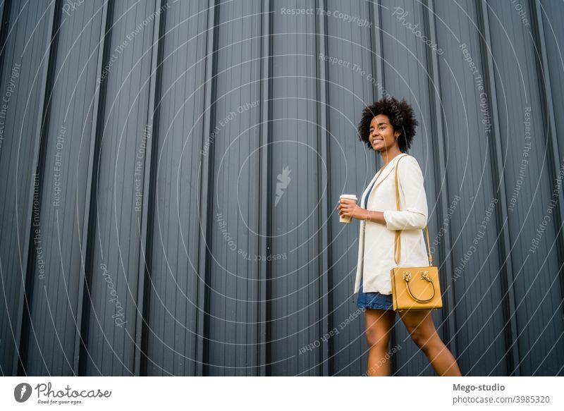 Porträt einer afroamerikanischen Geschäftsfrau beim Gehen im Freien. Afro-Look Business Frau urban Lächeln Erwachsener Kaffee Kaffee zum Mitnehmen Anzug