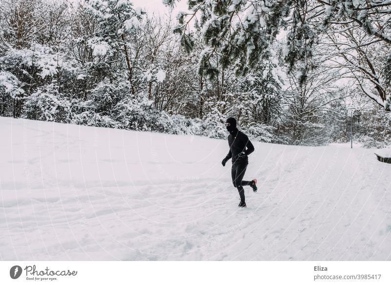 Ein Mann joggt im Winter durch den Schnee joggen laufen Sport Fitness Bewegung sportlich Park Natur Schneelandschaft Läufer Training Joggen Jogger