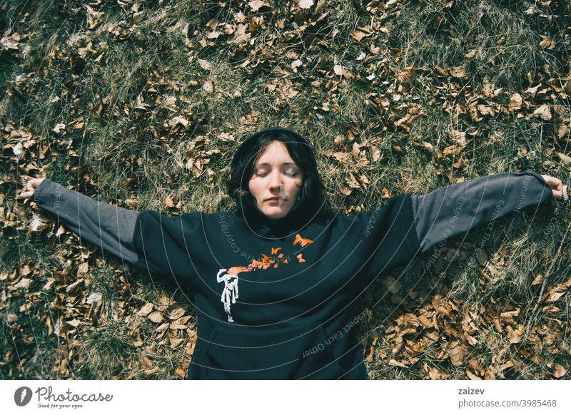 Ein Mädchen mit geschlossenen Augen liegend ruht in der Natur Frau Dame jung Teenager aussruhen Lügen nach unten Boden Ruhe Windstille in aller Ruhe Stille