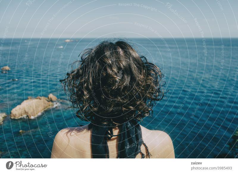 Ein Mädchen mit einem Kopftuch im Nacken und nacktem Rücken von hinten schaut auf den Horizont im Meer Costa Brava calella de palafrugell Palamos Frau Dame