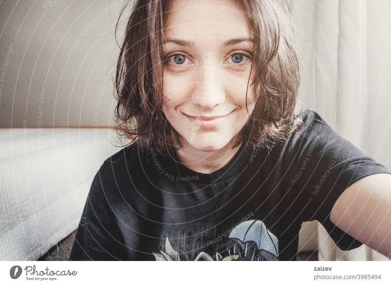 Mädchen mit kurzen Haaren und blauen Augen macht ein Selfie Menschen Frau eine Person im Innenbereich Teenager 20s 30s mittelgroß Textfreiraum Zentrum