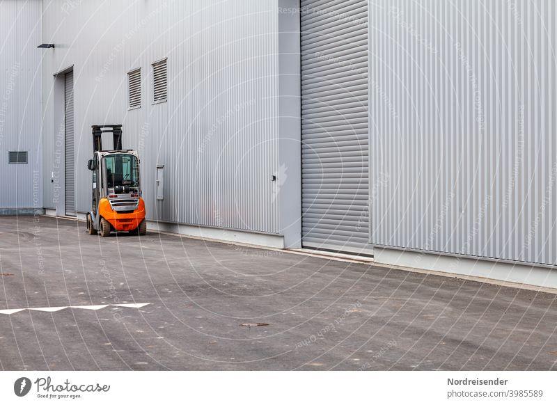 Gabelstapler vor einer modernen Industriefassade gabelstapler fabrik logistik transport lager industrie beförderung laden last heben tor rolltor neu fertigung