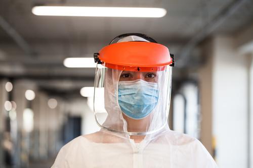 Porträt einer weiblichen Rettungssanitäterin mit persönlicher Schutzausrüstung, Gesichtsmaske und Gesichtsschild, stehend in einem Krankenhausflur oder -korridor