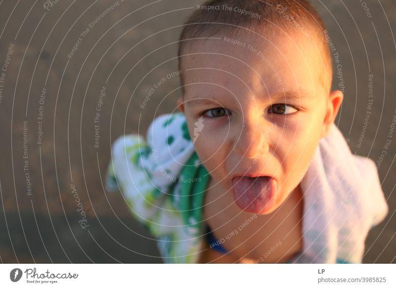 Kind streckt seine Zunge heraus Blick in die Kamera Porträt Oberkörper Sonnenuntergang Sonnenaufgang Sonnenstrahlen Sonnenlicht Licht Strukturen & Formen