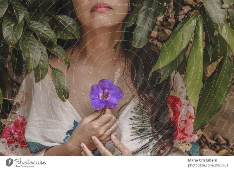 Frau trägt ein geblümtes Sommerkleid und hält eine Blume an der Brust, zeigt Konzept der Achtsamkeit, Meditation, Frühling Saison und Leben Neuanfänge Blüte