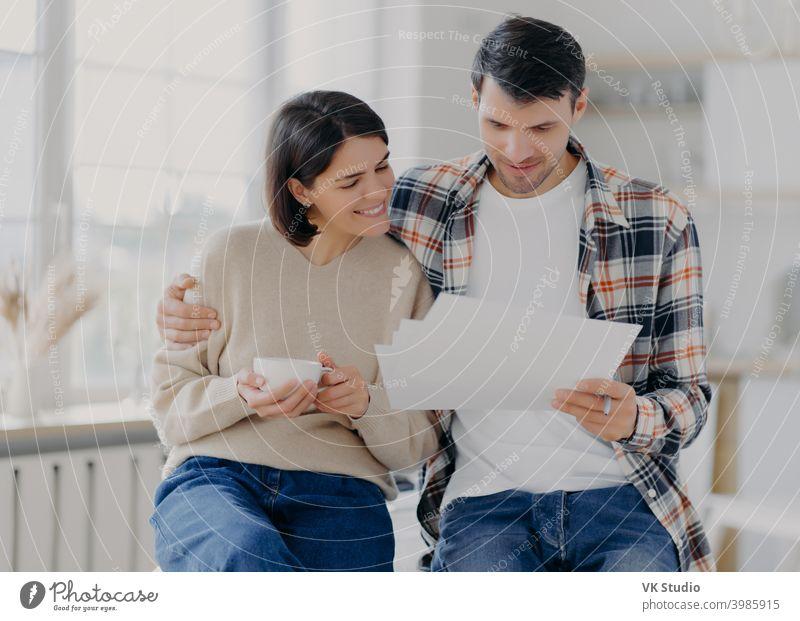 Caring Mann umarmt seine Frau, Blick durch Dokumente mit glücklichen Ausdrücke, Studie Zahlung Rechnungen, trinkt Kaffee, in Freizeitkleidung gekleidet, posieren in geräumigen Raum mit unscharfen Hintergrund. Familie und Arbeit