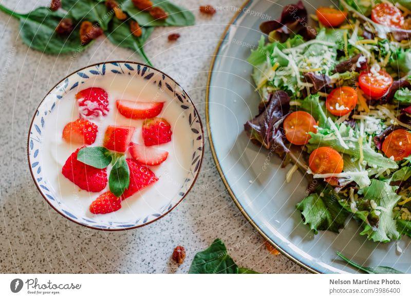 Nahaufnahme einer gesunden Mahlzeit aus Joghurt mit Erdbeeren, begleitet von einem Teller mit frischem Salat. Lebensmittel Gesundheit erdbeeren Tomaten