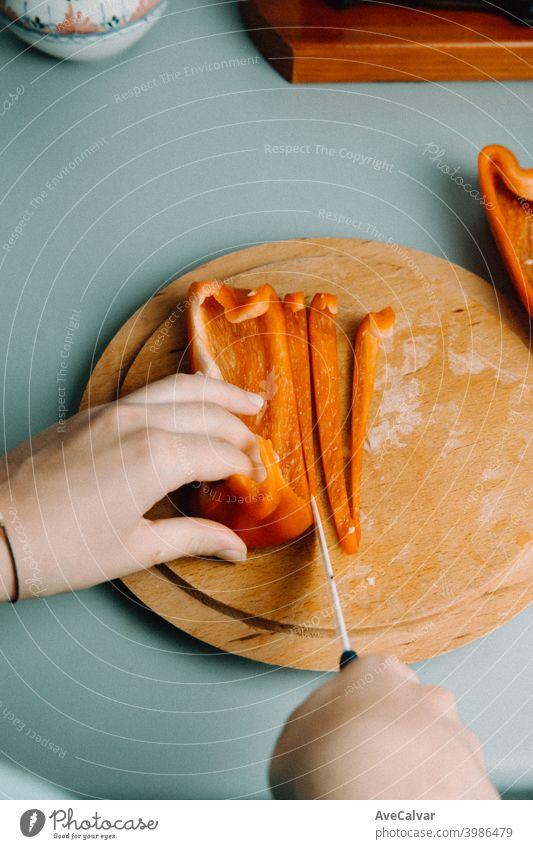 Eine Frau Schneiden einige Pfeffer über eine hölzerne runde Platte mit einem Messer beim Kochen mit der Pfanne in der Küche horizontal Arbeitsplatz Desktop