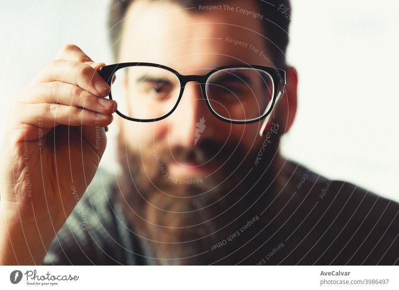 Ein unscharfes Hipster-Männchen, das eine Blaulichtbrille im Fokus der Kamera hält, während es lächelt 20s Kontemplation Unternehmer genial