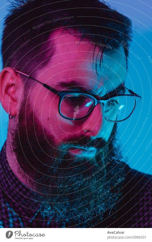 Ein junger Hipster-Mann mit blauer Lichtbrille schaut mit ernstem Gesicht auf blauen und rosa Farben zur Kamera weg 20s Kontemplation Unternehmer genial