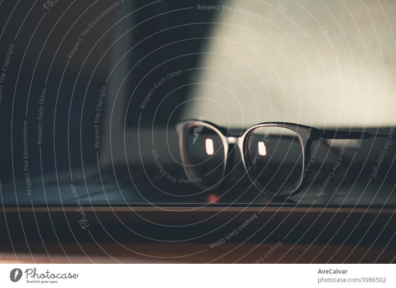 Eine Nahaufnahme von einigen Blaulichtbrillen über einem Laptop 20s Kontemplation Unternehmer genial Technik & Technologie Hipster Kopfschuss junger Erwachsener