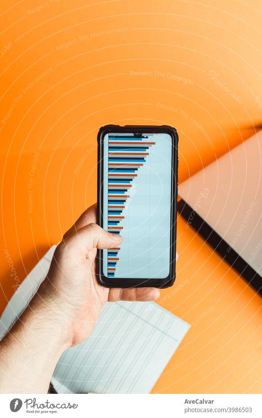 Eine Hand hält ein Telefon mit Statistiken über einen orangefarbenen Hintergrund mit Laptop und Notebook mit Finanzkonzept finanziell blanko Business Büro