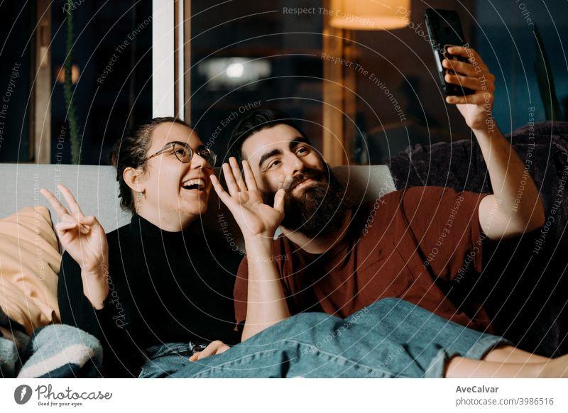 Ein junges Paar auf der Couch grüßt zum Handy und lächelt, während auf Pandemie anhänglich umarmend Humor Ehefrau Ehemann Foto Ethnizität lebend Partnerschaft