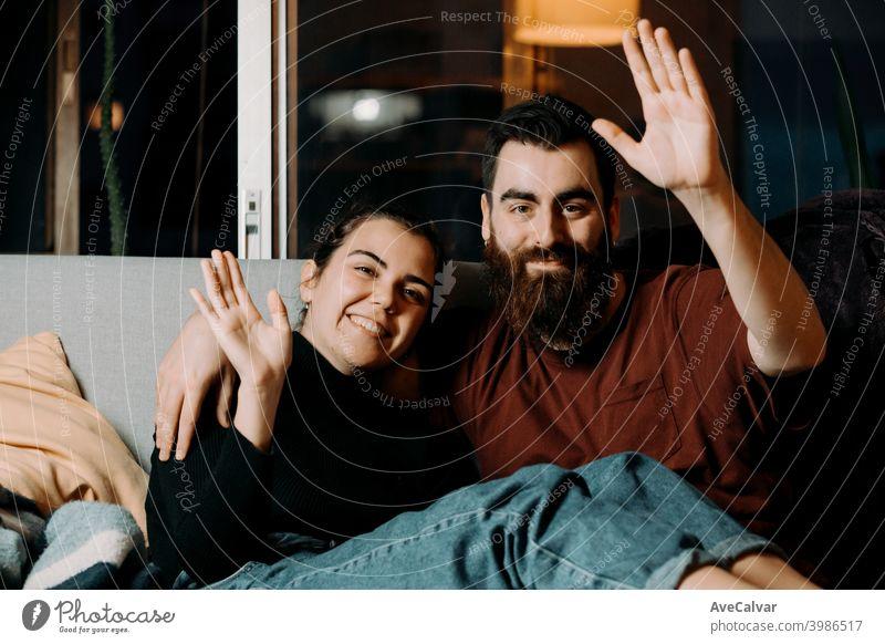 Ein junges Paar auf der Couch, das in die Kamera grüßt und lächelt, während es auf Pandemie anhänglich umarmend Humor Ehefrau Ehemann Foto Ethnizität lebend