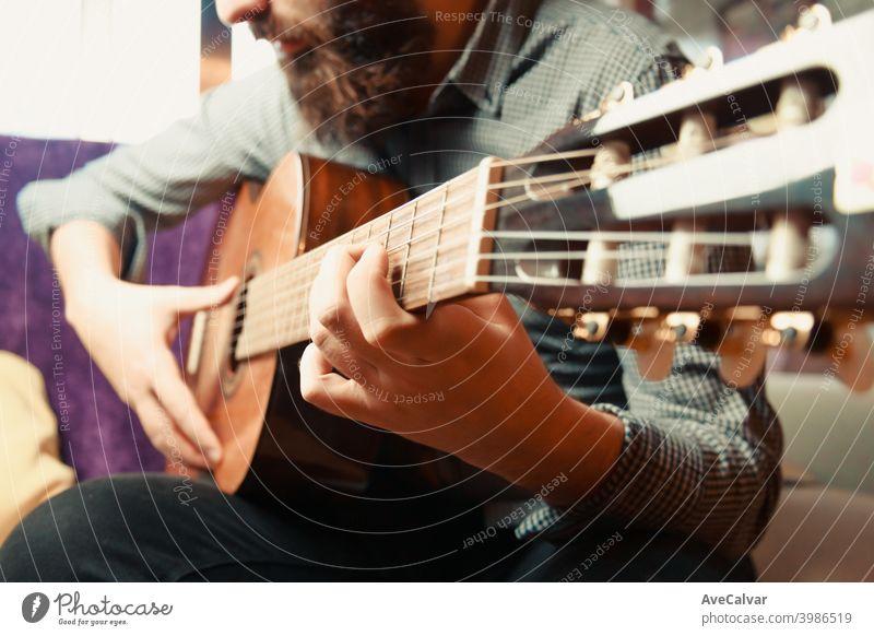 Eine Nahaufnahme der Hände eines bärtigen Mannes, der an einem hellen Tag spanische Gitarre spielt akustische Gitarre Kopierbereich Ausdrücken flippig Harmonie