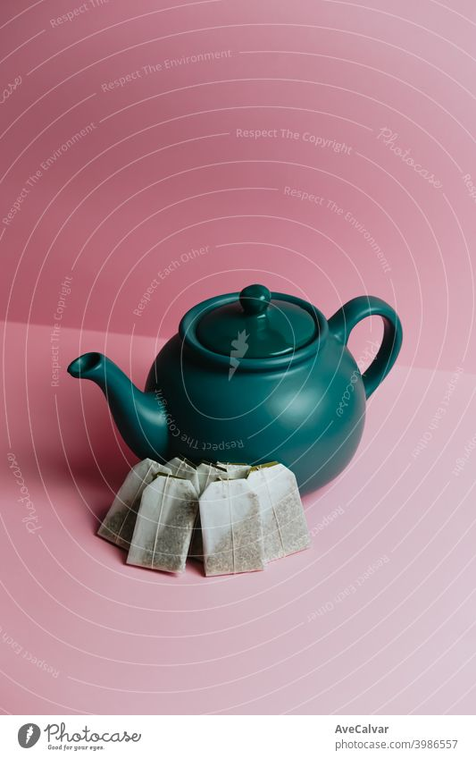 Eine minimalistische blaue Teekanne und schnelle Tee Umschläge über einen pastellrosa Hintergrund konzeptionell Kopierbereich Marketing karg graphisch Reichtum
