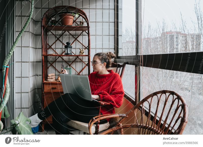 Eine junge Frau, die an seinem Laptop arbeitet, sitzt auf einem Holzstuhl auf einer Kristallgalerie während eines hellen Tages in der Stadt Dokumente horizontal
