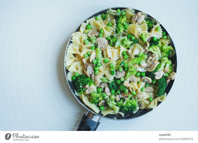 Pfanne mit gekochter schmackhafter italienischer vegetarischer Pasta mit Brokkoli, grünen Bohnen, Champignons in Sahnesoße. Schmackhaftes Mittag- oder Abendessen
