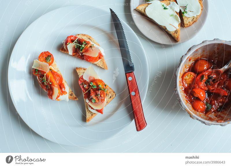 Köstliche italienische Vorspeise - Crostini-Toast mit gebackenen Kirschtomaten, Bauernkäse und Kräutern der Provence Belegtes Brot Tomate Lebensmittel