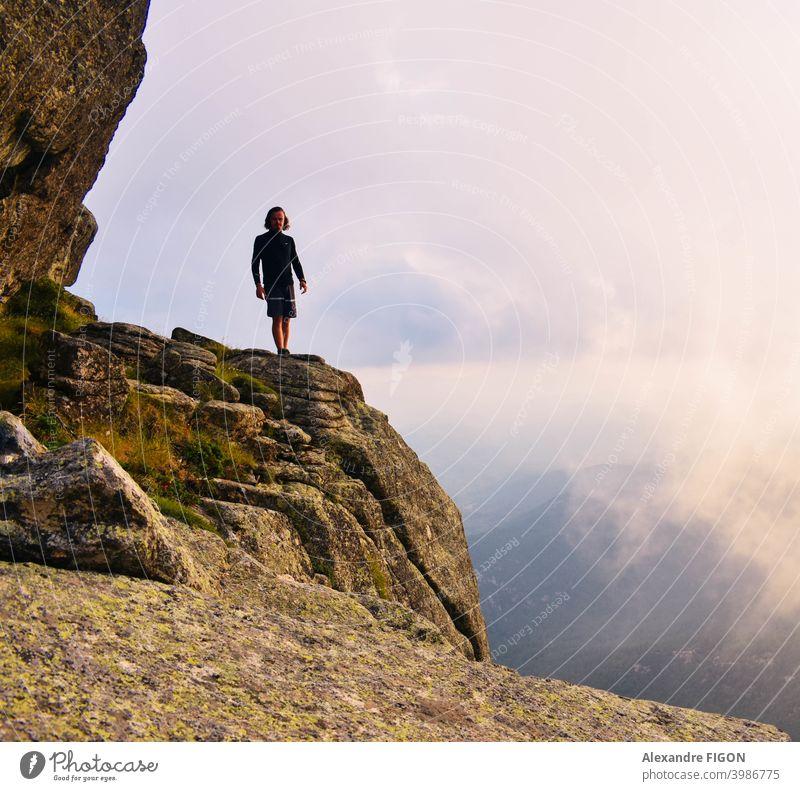 Ein Mann, der in den Bergen neben einem Canyon in Wolkenhöhe steht Berge u. Gebirge Gipfel Schlucht Wanderung Sonnenuntergang Steine farbenfroh Höhe